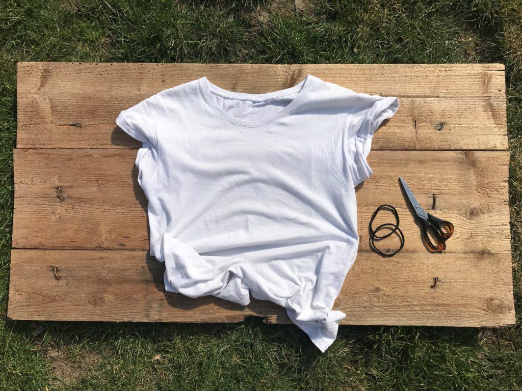 Vše, co potřebujete k výrobě roušky bez šití, jsou nůžky, straé triko a dvě gumičky.